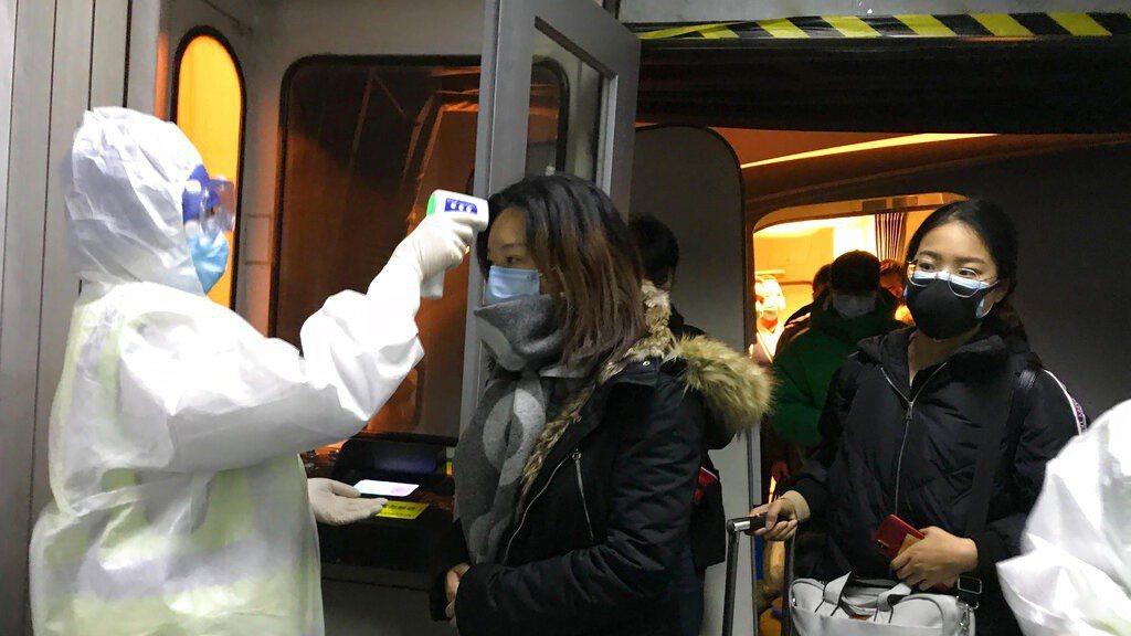 北京機場人員為武漢航班進行探測體溫。 美聯社