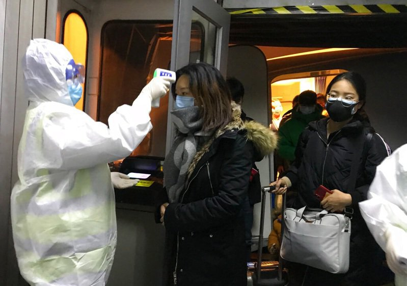 北京機場人員為武漢航班進行探測體溫。美聯社