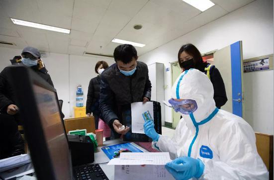 北京醫師身著防護服看診。每家醫院發燒門診大都排長龍,有的等了五小時還看不上,一些病患來回在各三甲醫院穿梭。中新社