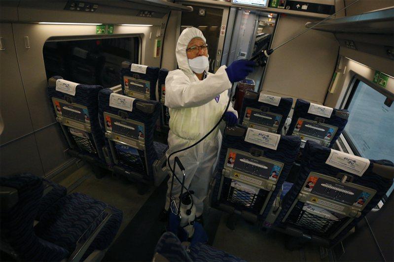 圖為一名韓國環衛工人在火車上噴灑消毒劑。歐新社