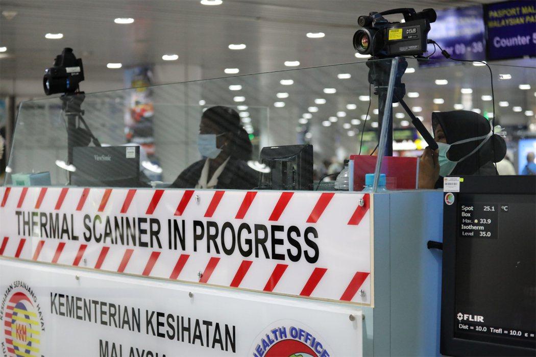 圖為雪邦吉隆坡國際機場,衛生檢疫人員觀測檢視旅客體溫。路透社