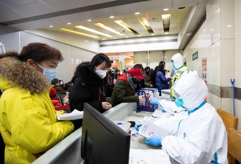大陸多個省市陸續出現新型冠狀病毒肺炎的感染個案,不少醫護人員疲於奔命;圖為武漢醫院的醫護人員接待求診者。中新社