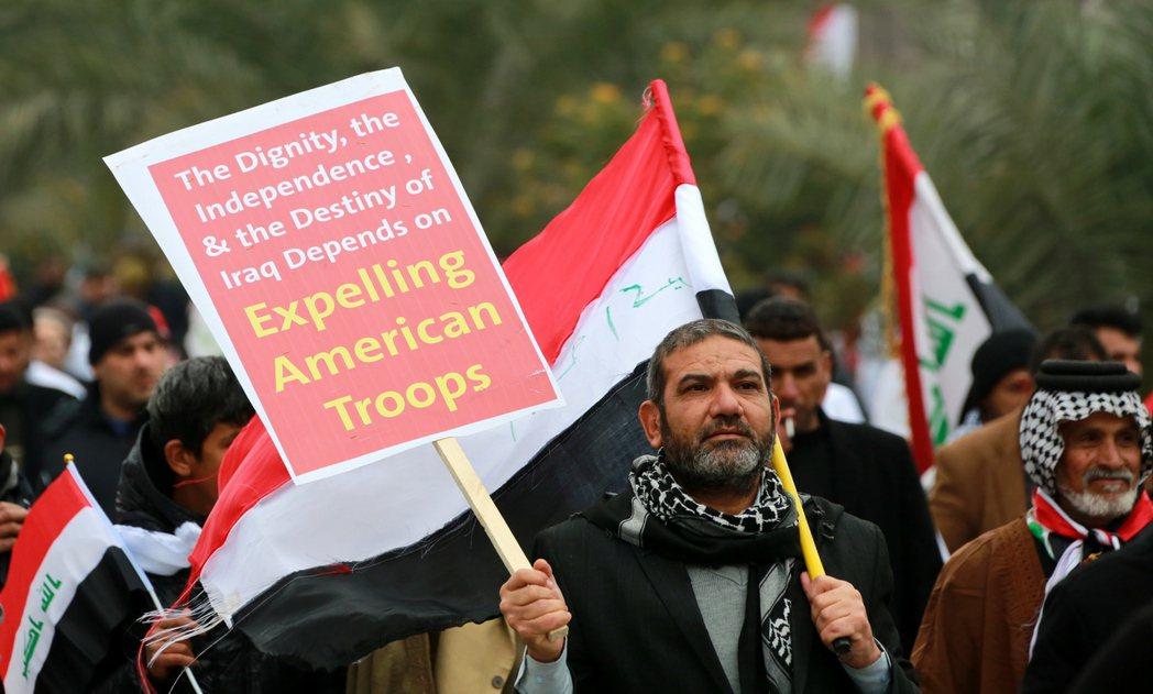 一名薩德爾支持者手持「驅逐美國部隊」的標語及伊拉克國旗。(歐新社)