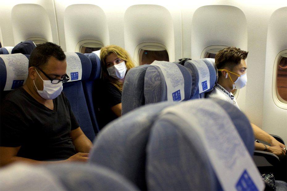 圖為從澳洲雪梨飛往北京的班機上,乘客紛紛戴起口罩。 路透