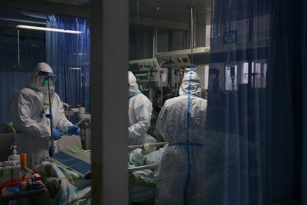 圖為武漢大學中南醫院重症醫學科一處病區23日景象,醫護人員正在救治一名新型冠狀病...
