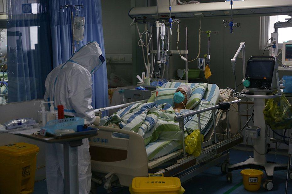 圖為武漢大學中南醫院重症醫學科一處病區23日景象,醫護人員正在救治一名新型冠狀病毒感染肺炎的患者。(取自上海《澎湃新聞》)