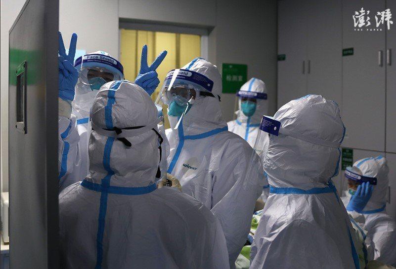圖為武漢中南醫院重症隔離病房醫護人員,對著鏡頭比出勝利手勢。(取自上海《澎拜新聞...