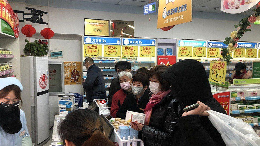 圖為武漢民眾在藥房內購買口罩等防疫用品 圖/取自《第一財經》