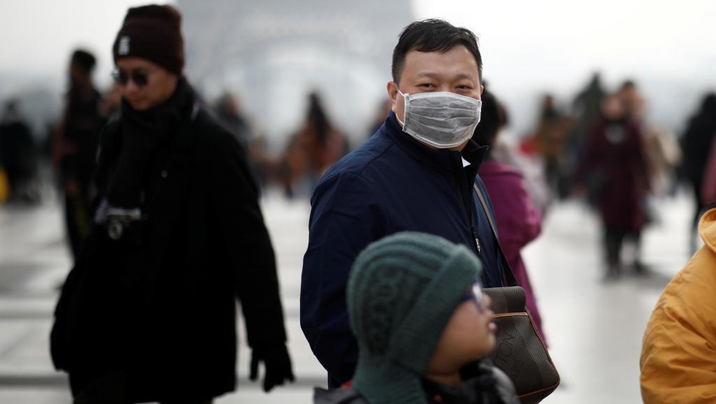 示意圖,一名佩戴口罩的亞洲男子在巴黎鐵塔前。 路透