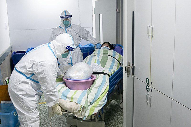 圖為武漢大學中南醫院重症隔離病房醫護人員,正將病情好轉的患者轉移至普通隔離病房。...