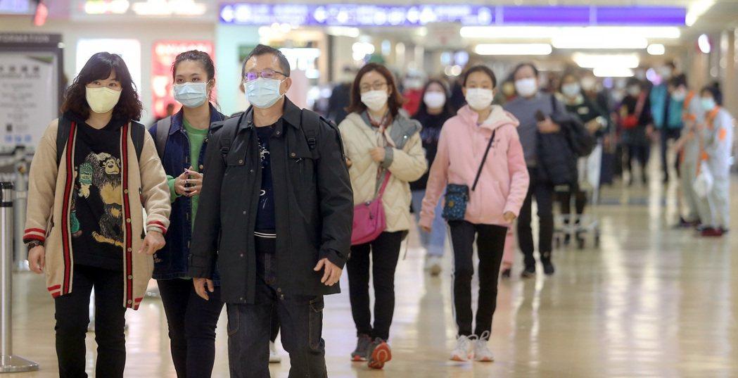 大陸武漢新型冠狀病毒肺炎疫情嚴峻,從大陸港澳等地航點搭機回台的旅客,戴口罩防疫的...