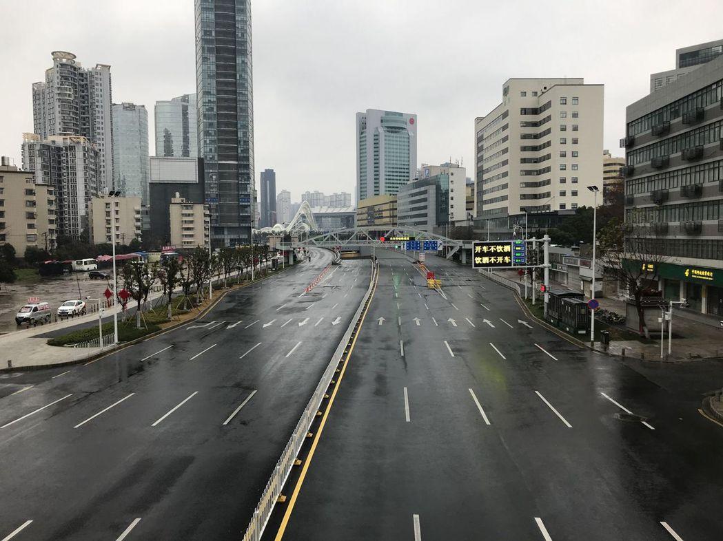 武漢為防疫,中心城區禁行私家車,廿六日的街頭一片空曠。(中新社)