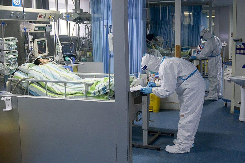 武漢大學中南醫院重症隔離病房,醫護人員身著防護衣為病人治療。新華社