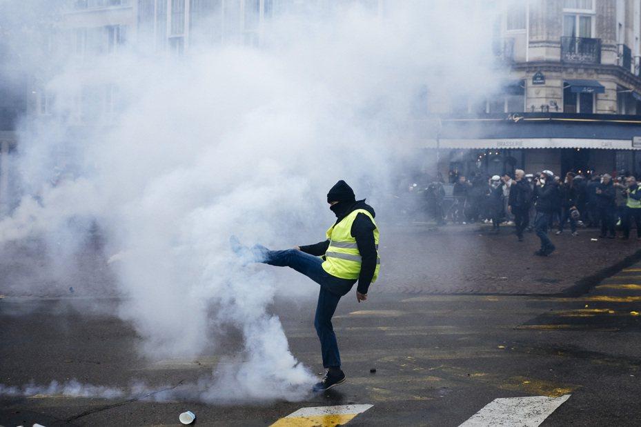 去年11月16日的巴黎黃背心示威周年活動中,一名示威者腳踢1枚催淚瓦斯彈。美聯社