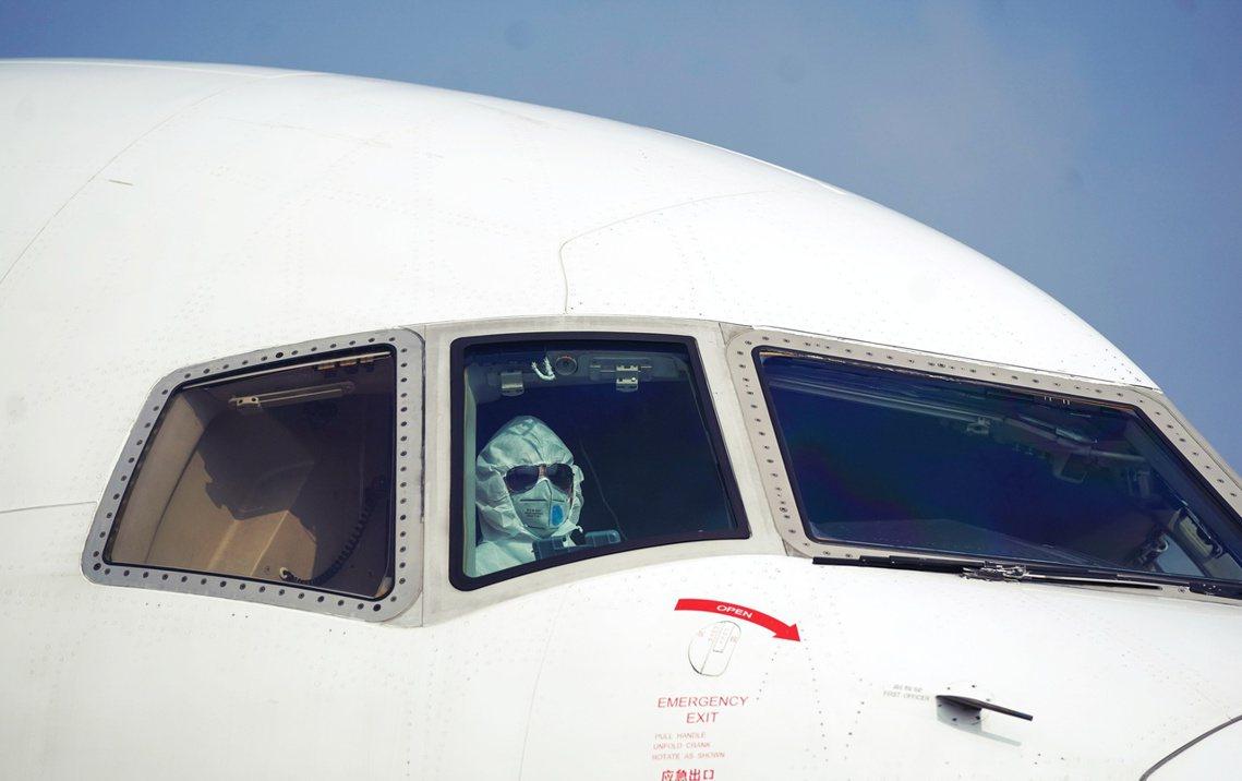 降落武漢機場的中國貨機,連機長也全副防疫武裝。 圖/美聯社