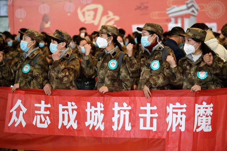 解放軍手拉「眾志成城抗擊病魔」標語,展現抗疫決心。 圖/新華社