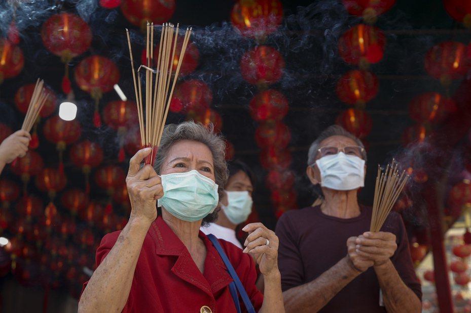 武漢肺炎疫情持續延燒,泰國曼谷中國城28日有民眾戴著口罩持香祈福。歐新社