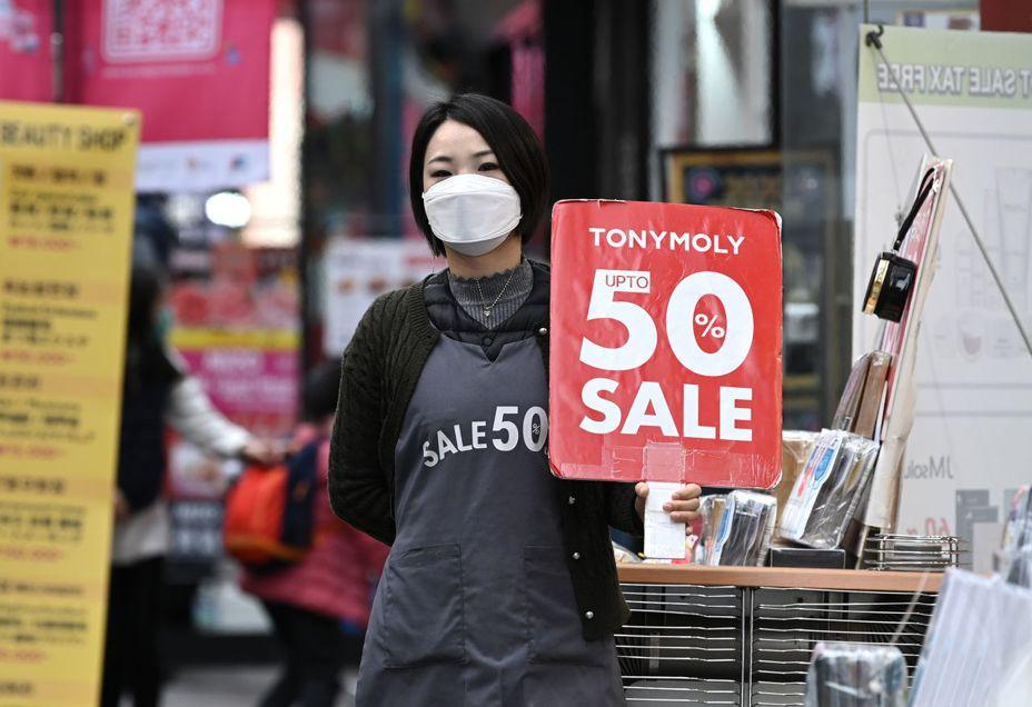 南韓明洞購物商圈的店家戴起口罩抗疫。法新社