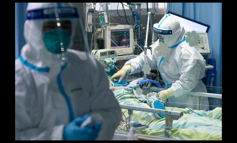武漢大學中南醫院重症隔離病房,醫護人員為病人治療。圖/取自新華社