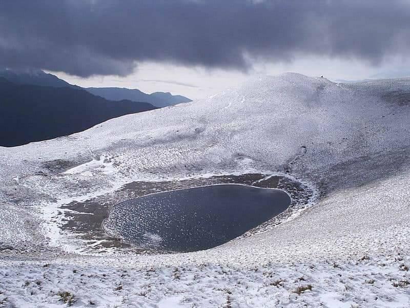 有「天使眼淚」美名的台東嘉明湖,因水氣充沛,加上氣溫低於零度,昨天凌晨開始飄雪,形成一片銀白美景。圖/台東林管處提供