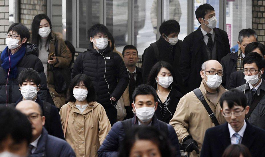 日本奈良街頭許多行人29日戴上口罩。 美聯社