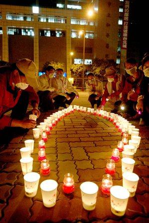 國際青商會員在和平醫院前點著圍繞成台灣形狀的蠟燭,為院內和SARS奮戰的醫護群及...