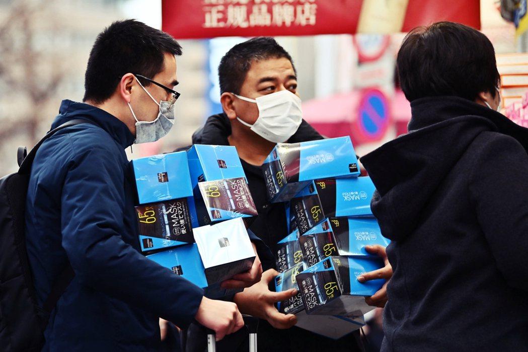 圖為1月27日,在東京秋葉原免稅商店中搶購口罩的中國觀光客。 圖/法新社