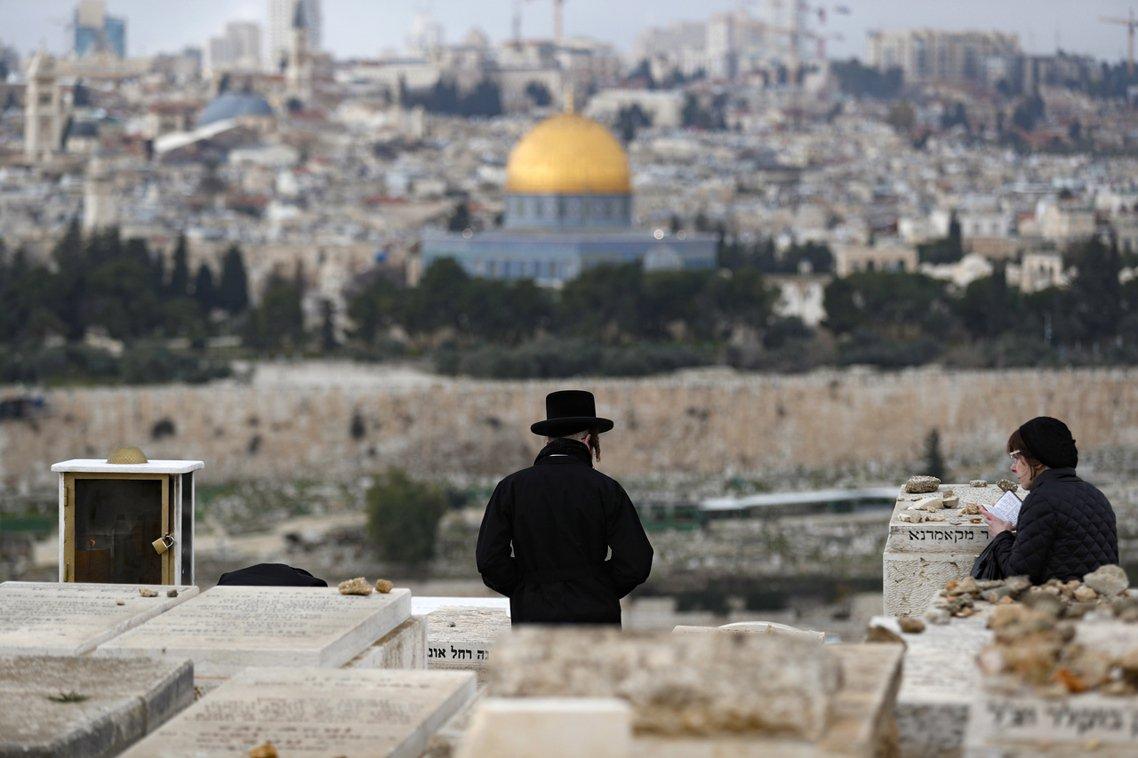 在東耶路撒冷的聖地「橄欖山」猶太墓園上,幾名以色列人正遠眺耶路撒冷的舊城心臟聖殿...
