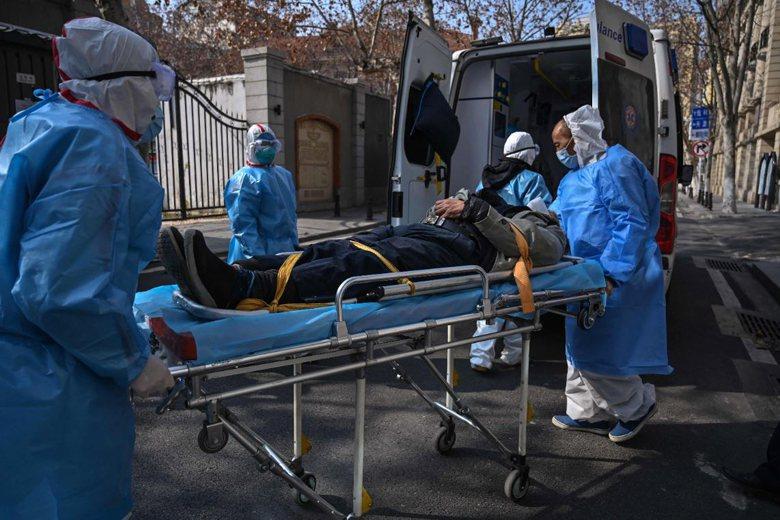 1月30日,著防護裝醫護人員將一名患者送上救護車。 圖/法新社