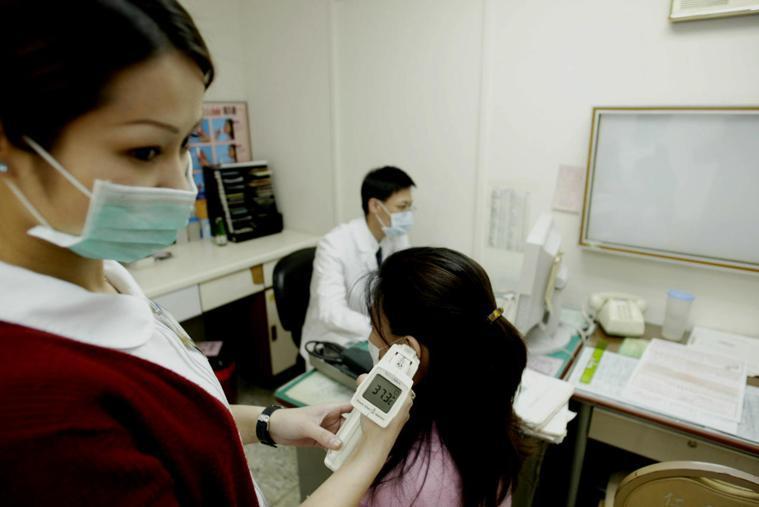 為看診的民眾測量耳溫 報系資料照 記者徐兆玄/攝影