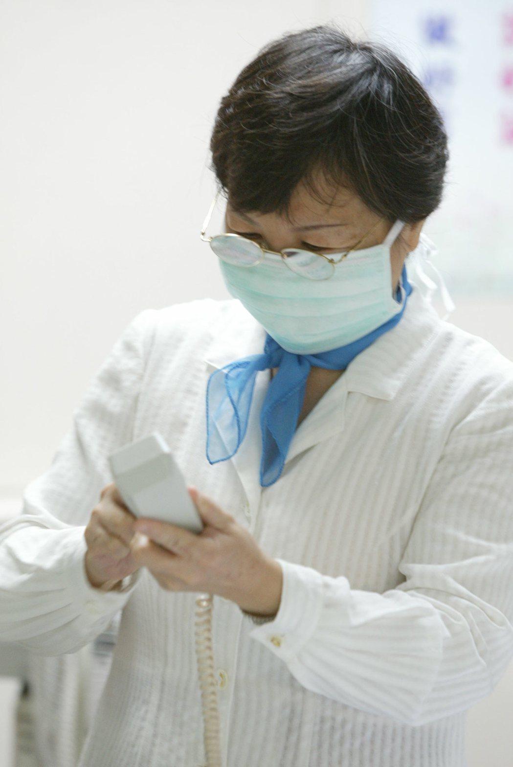醫院的工作人員都戴上了口罩並消毒院內的電話筒 報系資料照 記者邱德祥/攝影