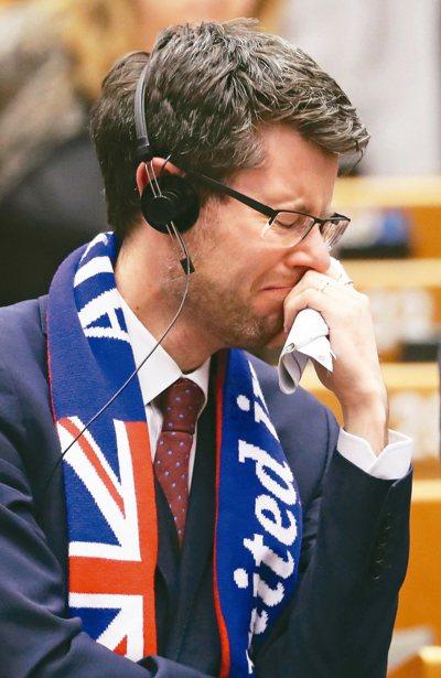 一名圍著英國國旗圖樣圍巾的歐洲議會議員感傷落淚。 (美聯社)