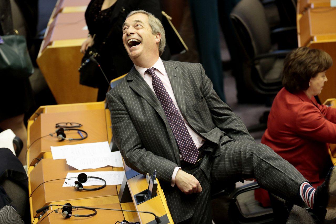 英國脫歐黨黨魁法拉吉廿九日在布魯塞爾的歐洲議會全體大會中,笑著向其他議員展示他的...