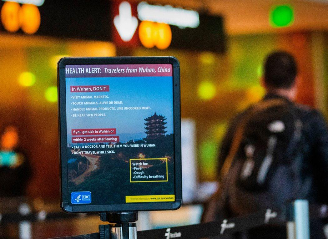 圖為西雅圖國際機場安檢站一處顯示冠狀病毒健康警報的標誌。 美聯社