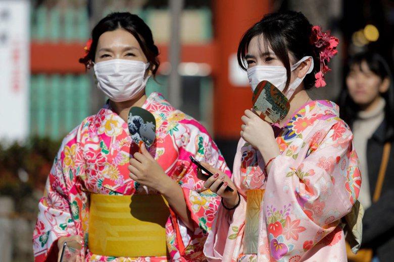 戴口罩仍預防飛沫傳染的主要方式。圖為日本民眾因應新型冠狀病毒疫情加溫戴上口罩。 圖/美聯社