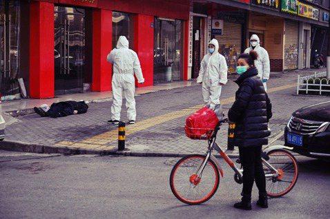 30日在武漢街頭,一名戴著口罩倒地不起的男子,被發現時已經身亡。醫護隨即全副防疫...