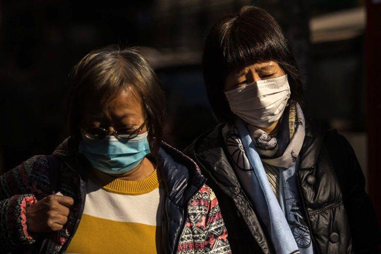 1月30日,香港民眾在街上戴上口罩防疫。 圖/法新社