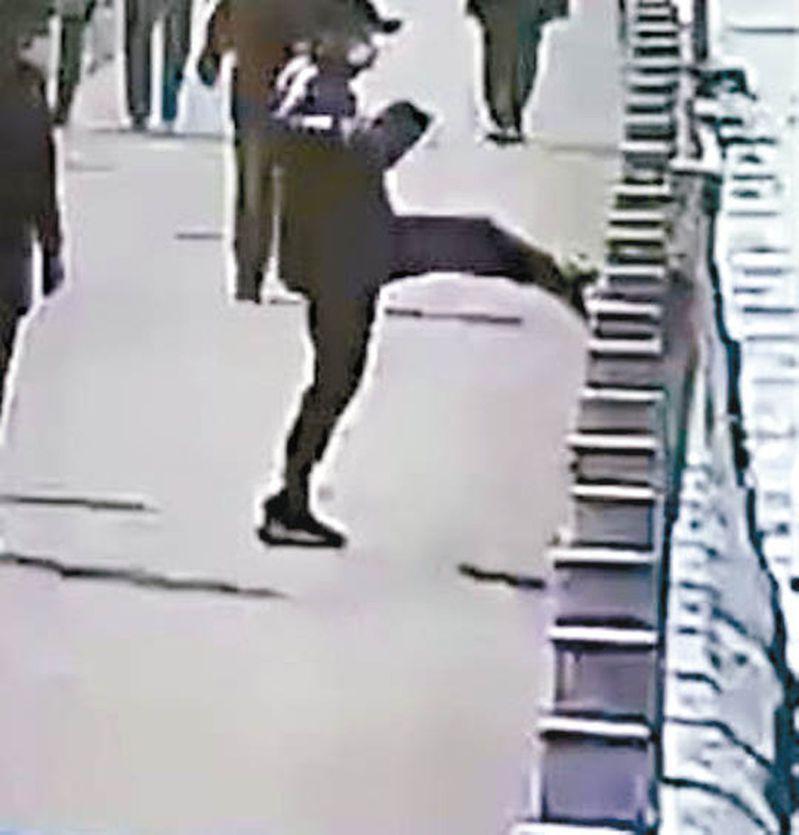 男子一腳踢向河邊護欄。視頻截圖