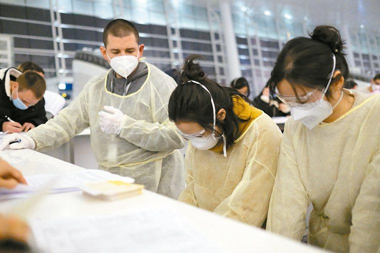 圖為戴口罩的旅客在武漢國際機場填寫文件。 美聯社