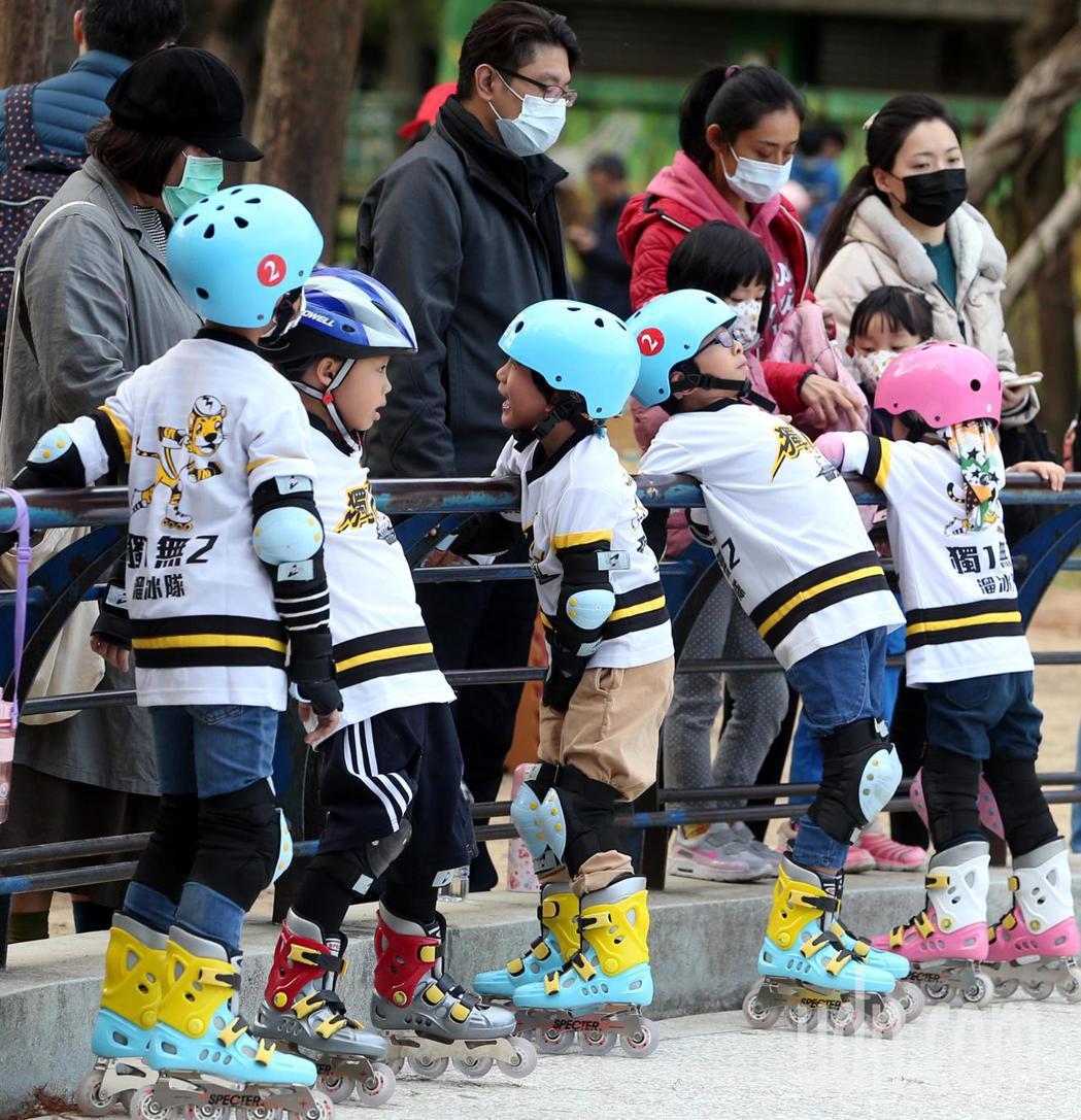 寒流威力減弱,氣溫回暖,吸引家長帶著小朋友到公園溜直排輪,場外的家長一律戴上口罩...