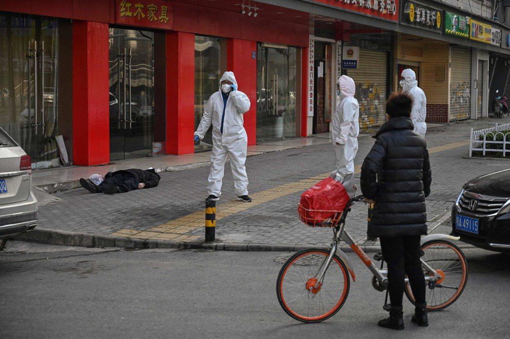 一名戴著口罩的路人30日在武漢一家醫院附近路邊倒地死亡,防護人員據報前往查看。(...