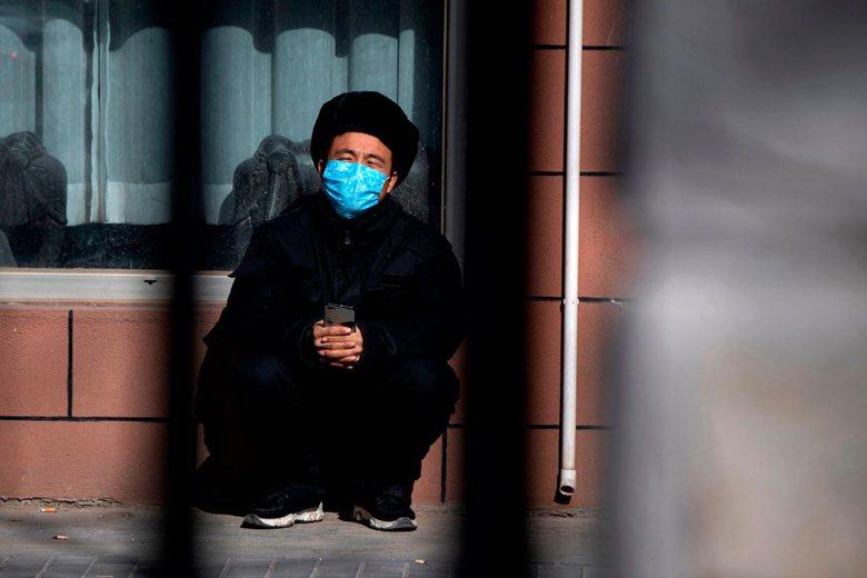 2月3日,一名戴上口罩的北京民眾蹲坐路旁。 圖/法新社