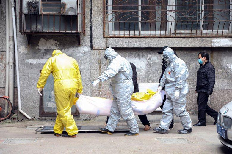 2月1日,武漢市殯儀館人員著防護裝,搬運一具疑似死於新型冠狀病毒遺體。 圖/美聯社