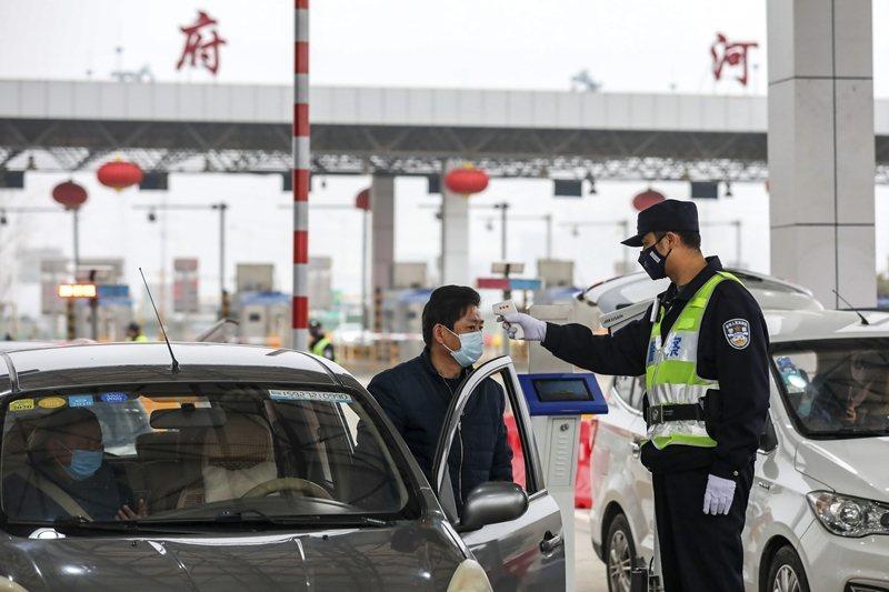 警察在高速公路收費站為通過的駕駛者與乘客測量體溫。攝於1月23日,武漢。 圖/美...