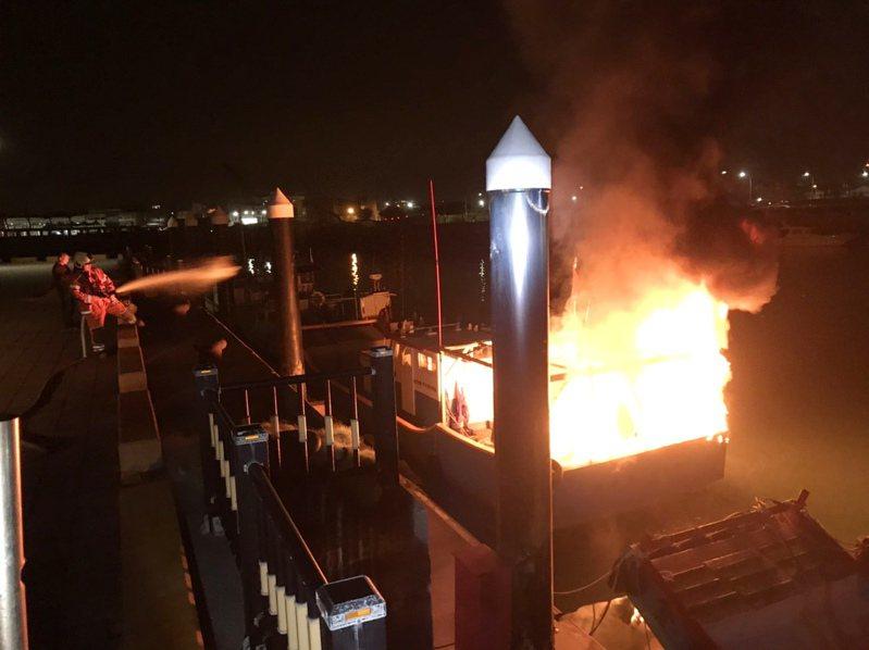 桃園市竹圍漁港停靠一艘膠筏漁船冒煙起火,燃燒猛烈,漁船漁網漁具付之一炬。圖/海巡署第八岸巡隊提供