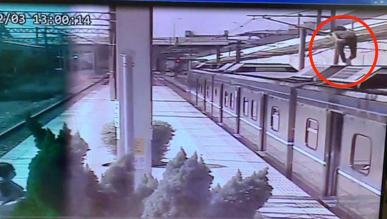 高雄市伍姓男子今天下午1時許在烏日車站爬上電車車廂,遭高壓電電擊送醫,監視器拍下驚險一瞬間。圖/讀者提供