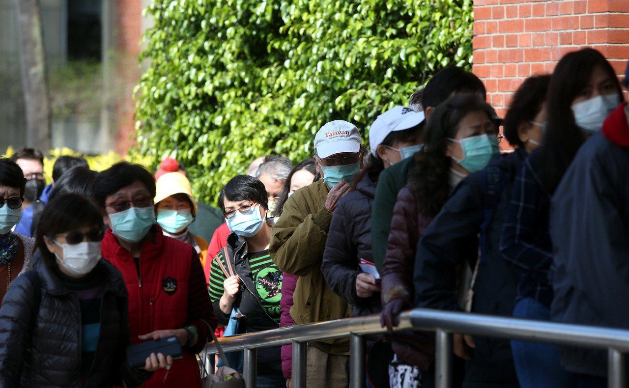 圖為民眾戴口罩在台大醫院舊院區門口大排長龍,要進去的和離開的及擠在門口買口罩的全...