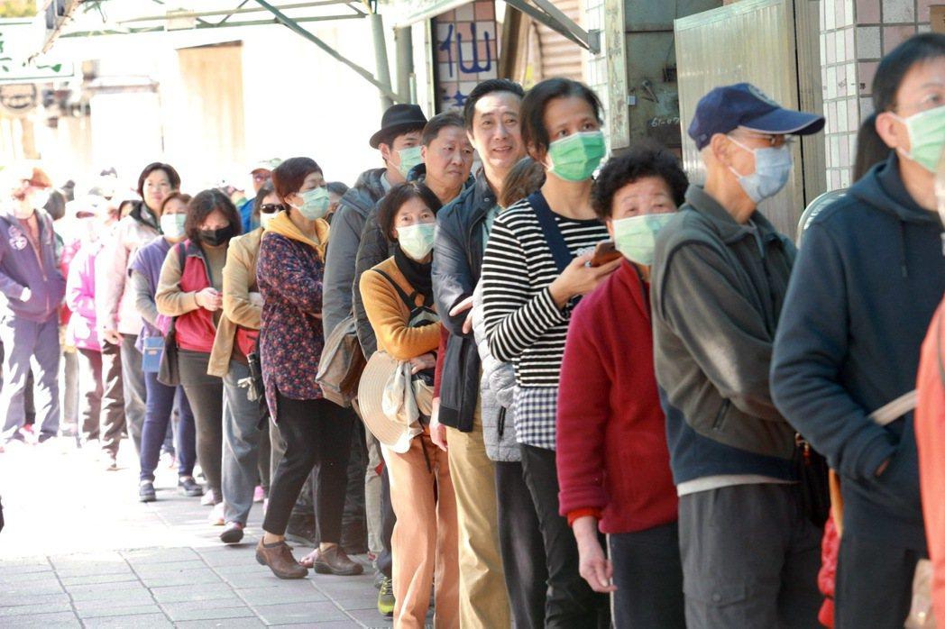 武漢肺炎持續肆虐,民眾為求自保一早就到口罩通路商外排隊搶買口罩,一家藥粧店正好物...