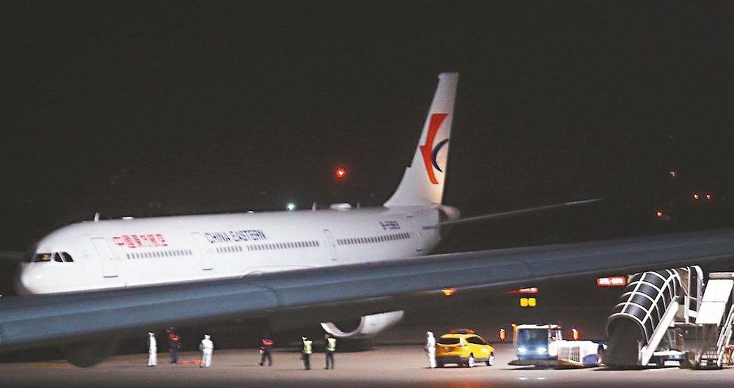 中國武漢返台包機昨晚近午夜抵台,由拖車拖行進入台灣飛機維修公司修護廠棚下客。記者...
