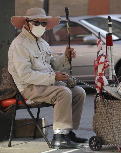 美國舊金山中國城一名街頭藝人戴口罩拉胡琴。 (美聯社)